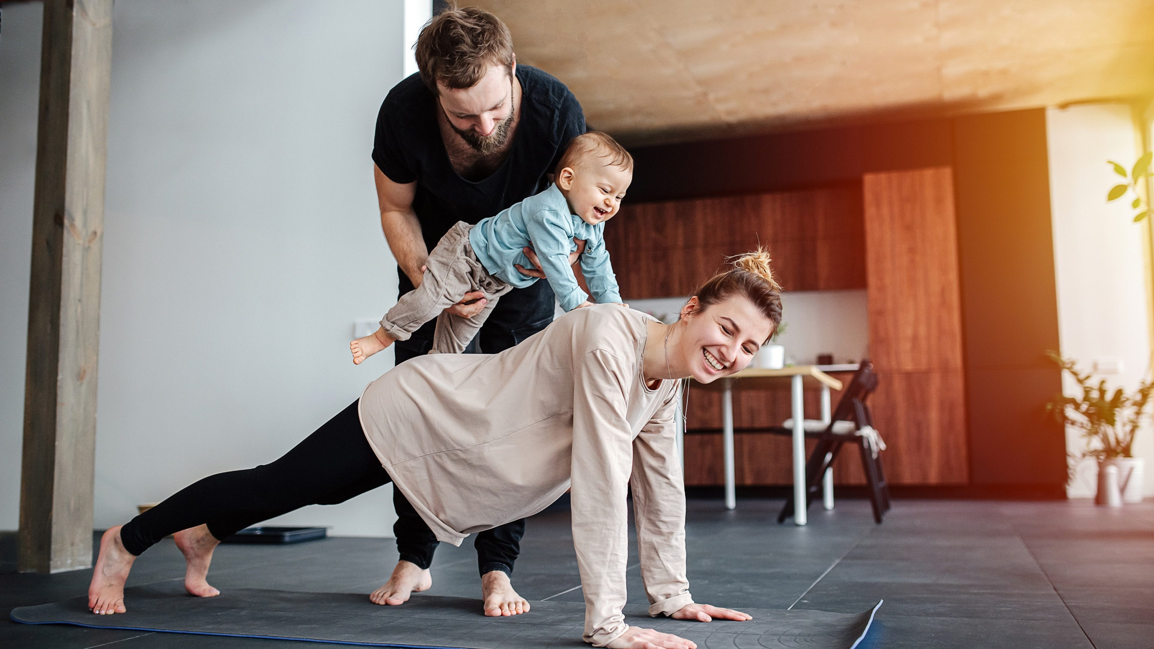 Family morning exercise. Mother doing plank, father holding their baby on her back, so he would ride her, including child in activity. Family quarantine, domestic life in self-isolation. Sunset light from the windows.